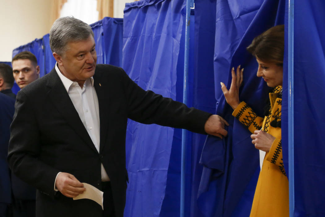 Ukrainian President Petro Poroshenko helps his wife Maryna to leave a booth at a polling statio ...