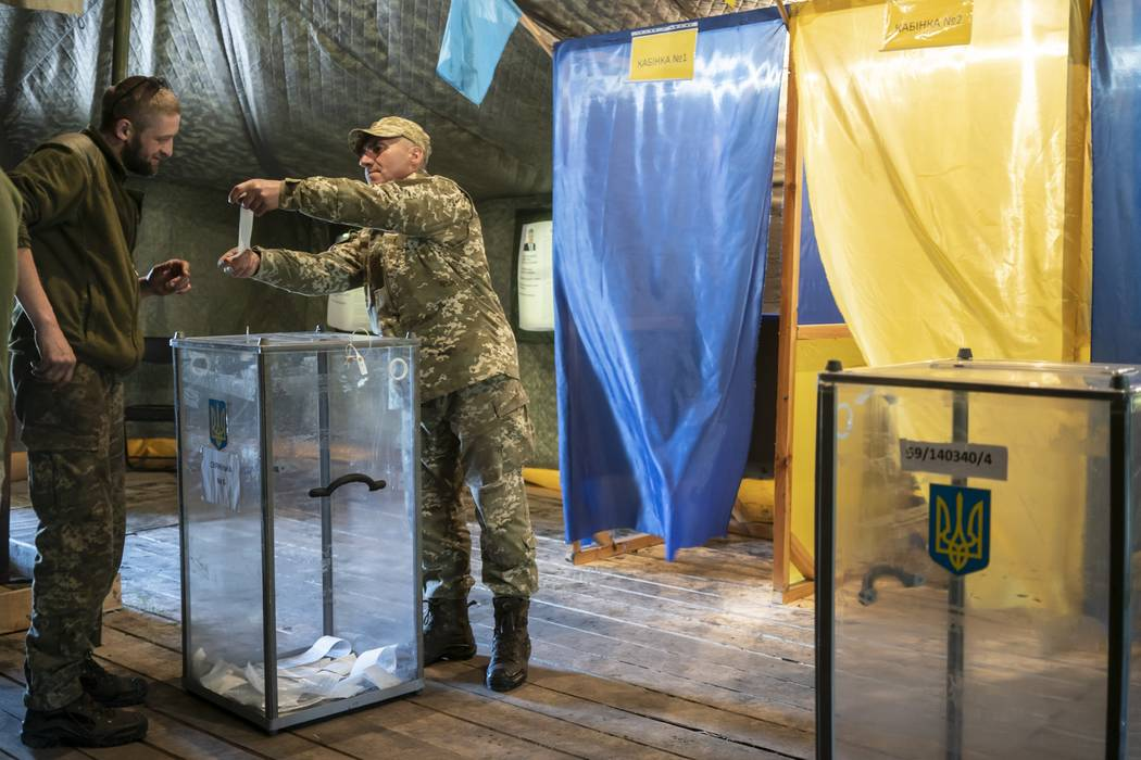 A Ukrainian government soldier demonstrates his ballot at a polling station, during the second ...