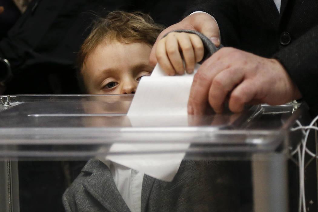 Ukrainian President Petro Poroshenko casts his ballot as his grandson Petro, looks at the ballo ...