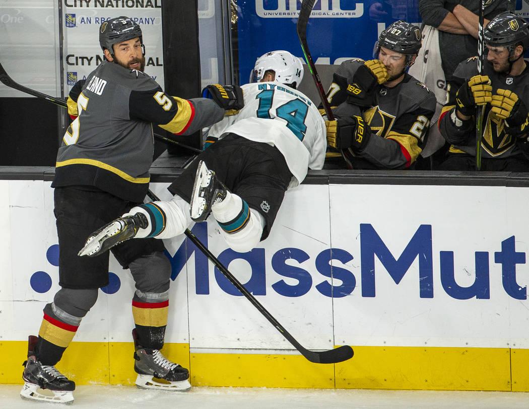 Golden Knights defenseman Deryk Engelland (5) drives San Jose Sharks center Gustav Nyquist (14) ...
