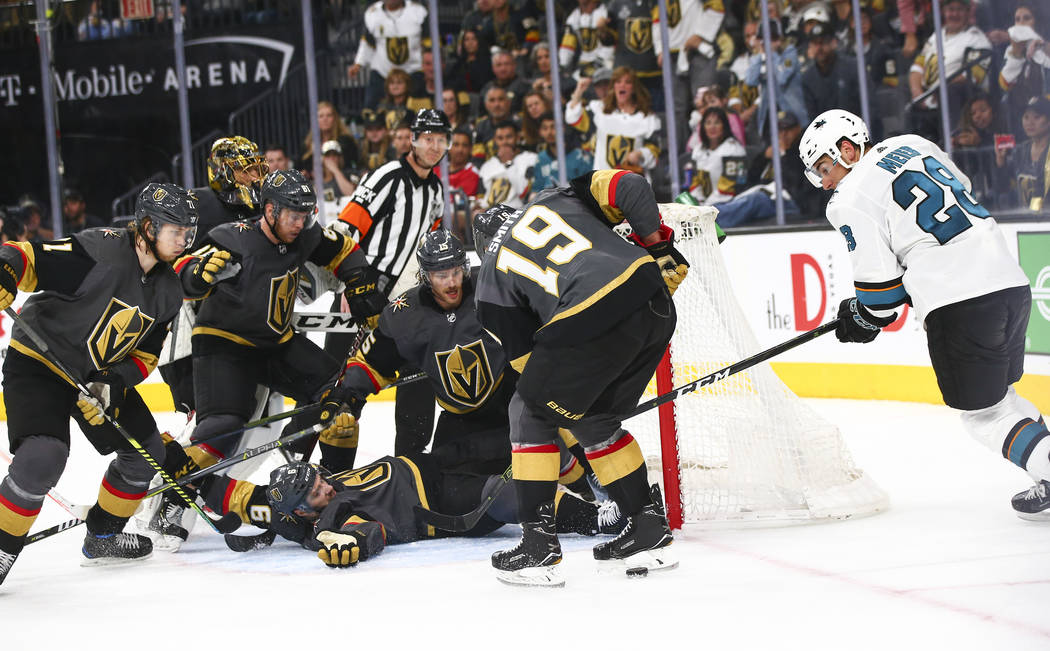 A phalanx of Golden Knights players surround the net in order to get the puck out as San Jose S ...