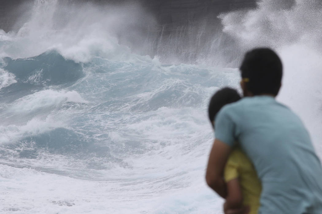 A man and his son watch as waves crash off sea cliffs along the southeast shore of Oahu as Hurr ...