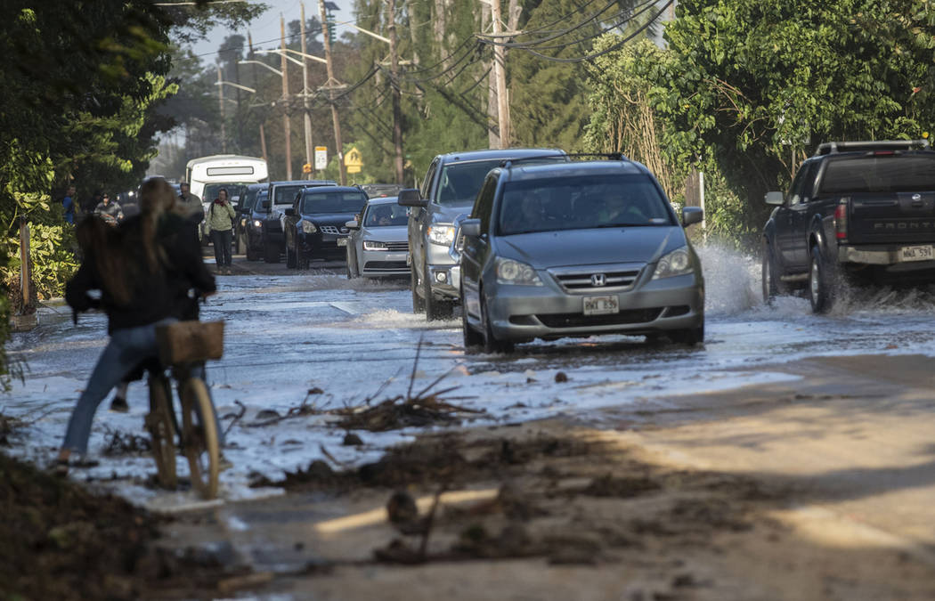 Vehicles pass through surf that washed over a roadway on Oahu's north shore near Haleiwa, Hawai ...