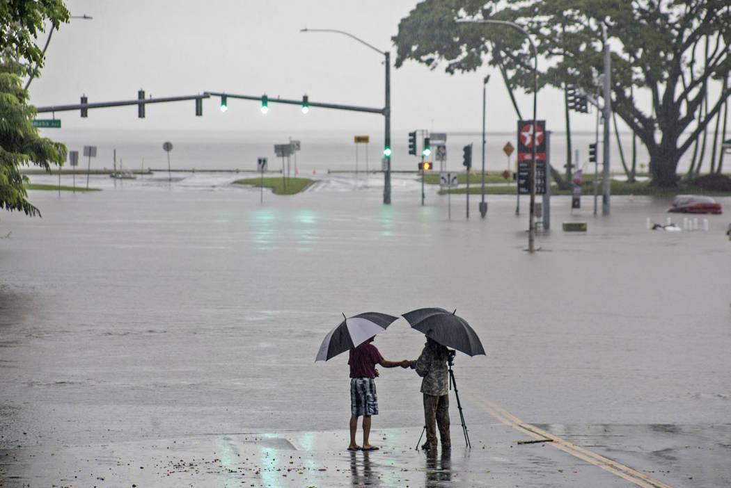 Ppeople stand near flood waters from Hurricane Lane in Hilo, Hawaii, in August 2018. (Hollyn Jo ...