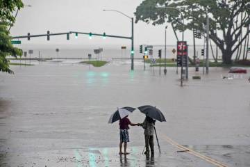 Ppeople stand near flood waters from Hurricane Lane in Hilo, Hawaii, in August 2018. (Hollyn Jo ...