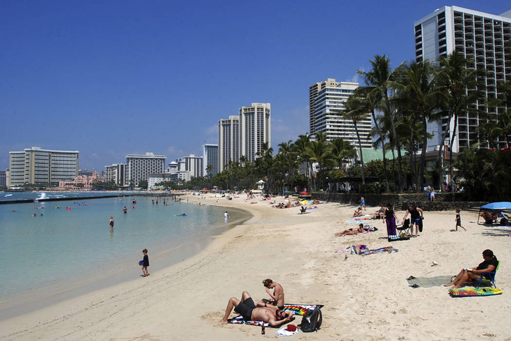 People relax on the beach in Waikiki in Honolulu in March 2017. (AP Photo/Caleb Jones)