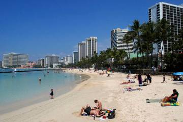 People relax on the beach in Waikiki in Honolulu in March 2017. (AP Photo/Caleb Jones)