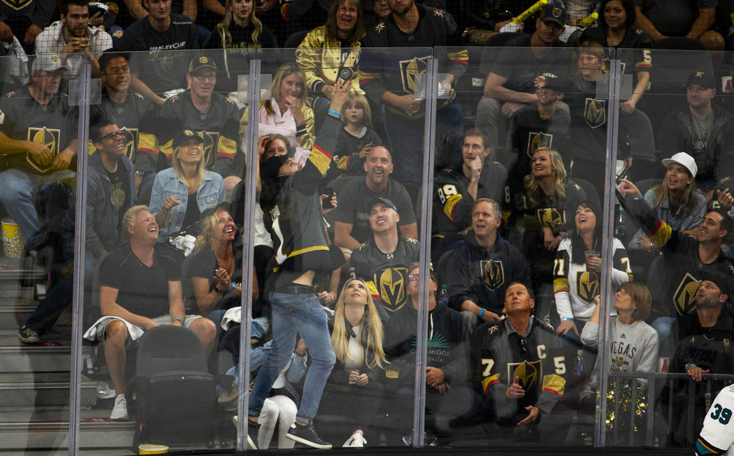 A fan reaches up for a puck that goes over the glass during the second overtime period of Game ...