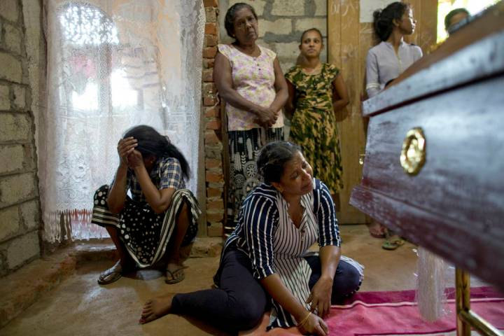 Relatives weep near the coffin with the remains of 12-year Sneha Savindi, who was a victim of E ...
