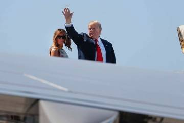 President Donald Trump, right, waves as he and first lady Melania Trump board Air Force One pri ...