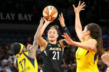 Las Vegas Aces guard Kayla McBride (21) takes a shot through Indiana Fever guard Erica Wheeler ...