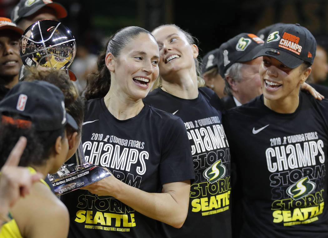 Seattle Storm guard Sue Bird, left, holds the championship trophy with her teammates during aft ...