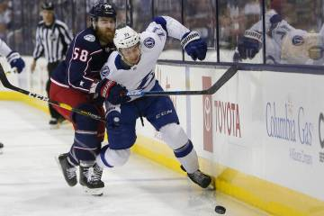 Columbus Blue Jackets' David Savard, left, checks Tampa Bay Lightning's Anthony Cirelli during ...