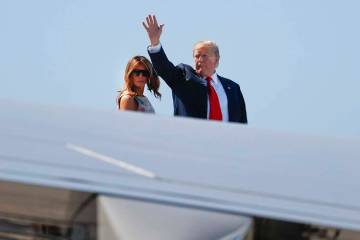 President Donald Trump waves as he and first lady Melania Trump board Air Force One prior to de ...