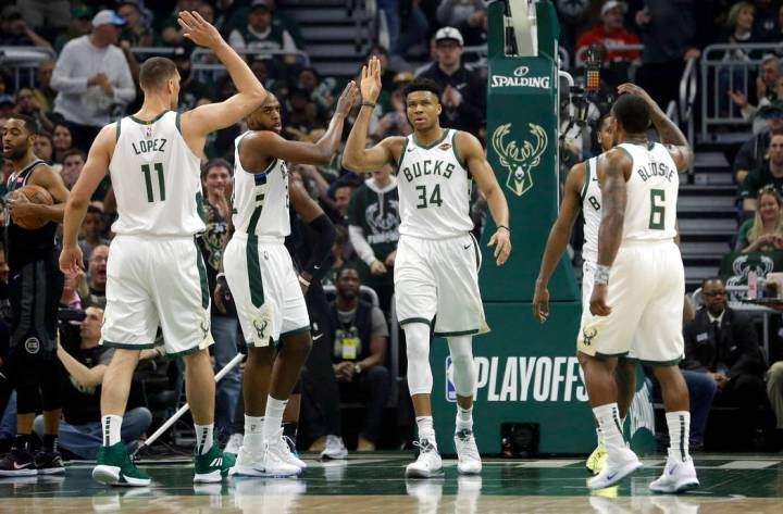 Milwaukee Bucks' Giannis Antetokounmpo gives high-fives to his teammates during the first half ...