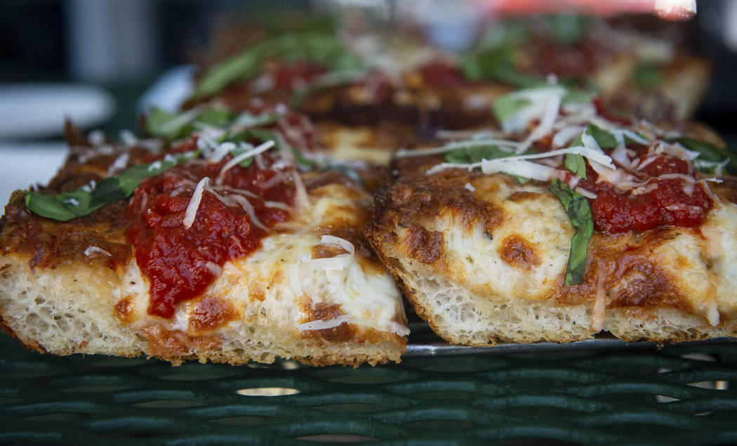 A slice of Detroit-style cheese pizza, left, sits next to a gluten-free slice of Detroit-style ...