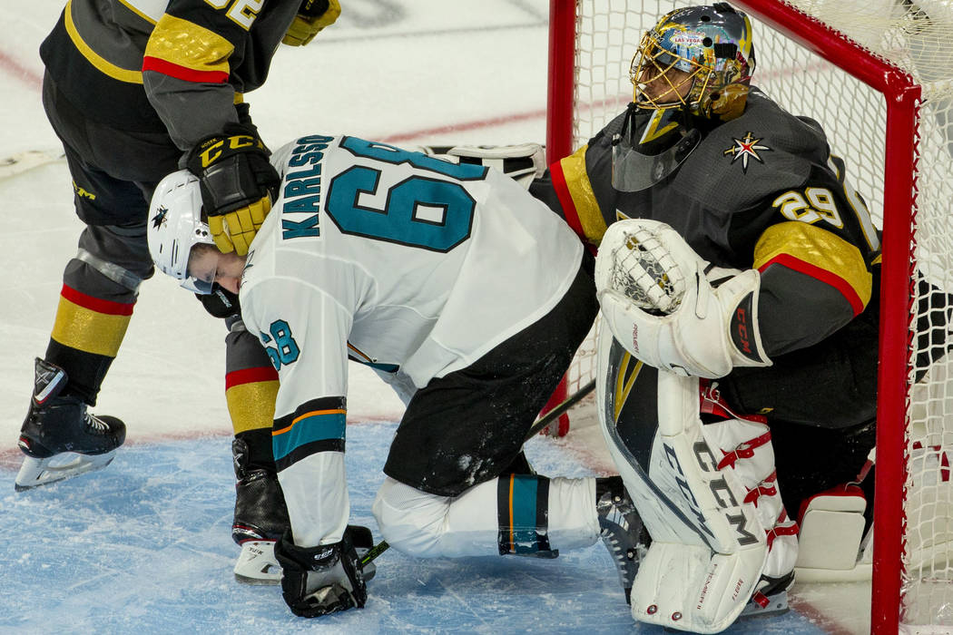 San Jose Sharks center Melker Karlsson (68) is pushed away by Golden Knights goaltender Marc-An ...