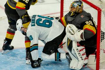 San Jose Sharks center Melker Karlsson (68) is pushed away by Golden Knights goaltender Marc-An ...
