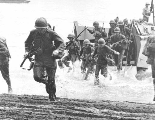 FILE - In this Aug. 1942 file photo, U.S. Marines charge ashore on Guadalcanal Island from a la ...
