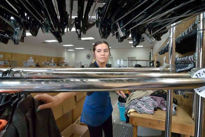 Merchandise processor Kassandra Van Duyne hangs sorted clothes in the warehouse at the Goodwill ...
