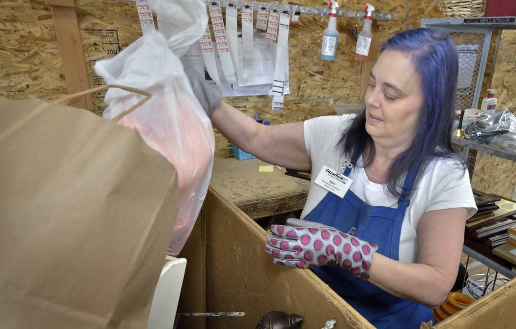 Merchandise processor Mary Smith sorts through donations in the warehouse at the Goodwill Thrif ...