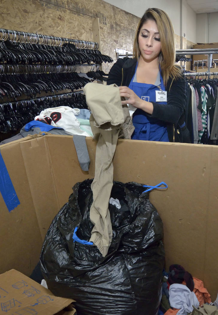 Merchandise processor Jessica Estrada sorts through clothes in the warehouse at the Goodwill Th ...