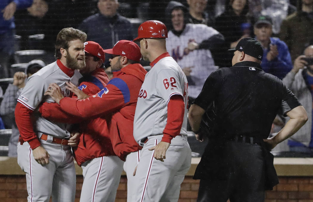 Philadelphia Phillies' Bryce Harper, left, is restrained while arguing with umpire Mark Carlson ...
