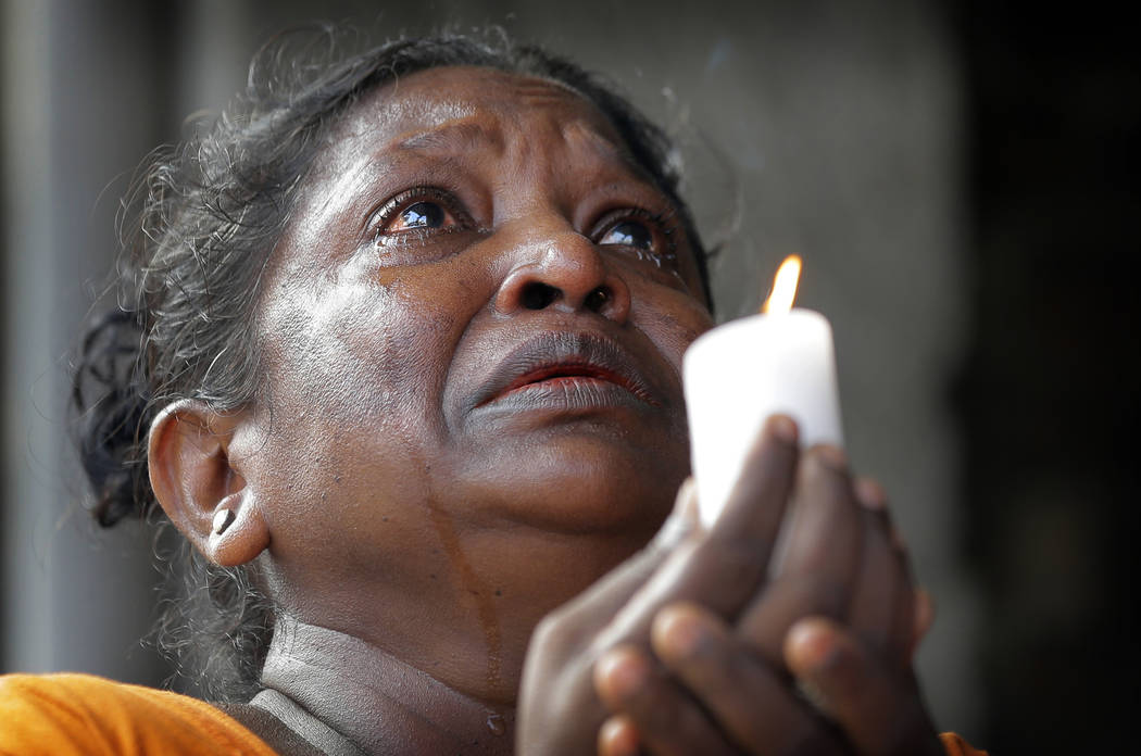 A Sri Lankan roman catholic woman prays during a three minute nationwide silence observe to pay ...