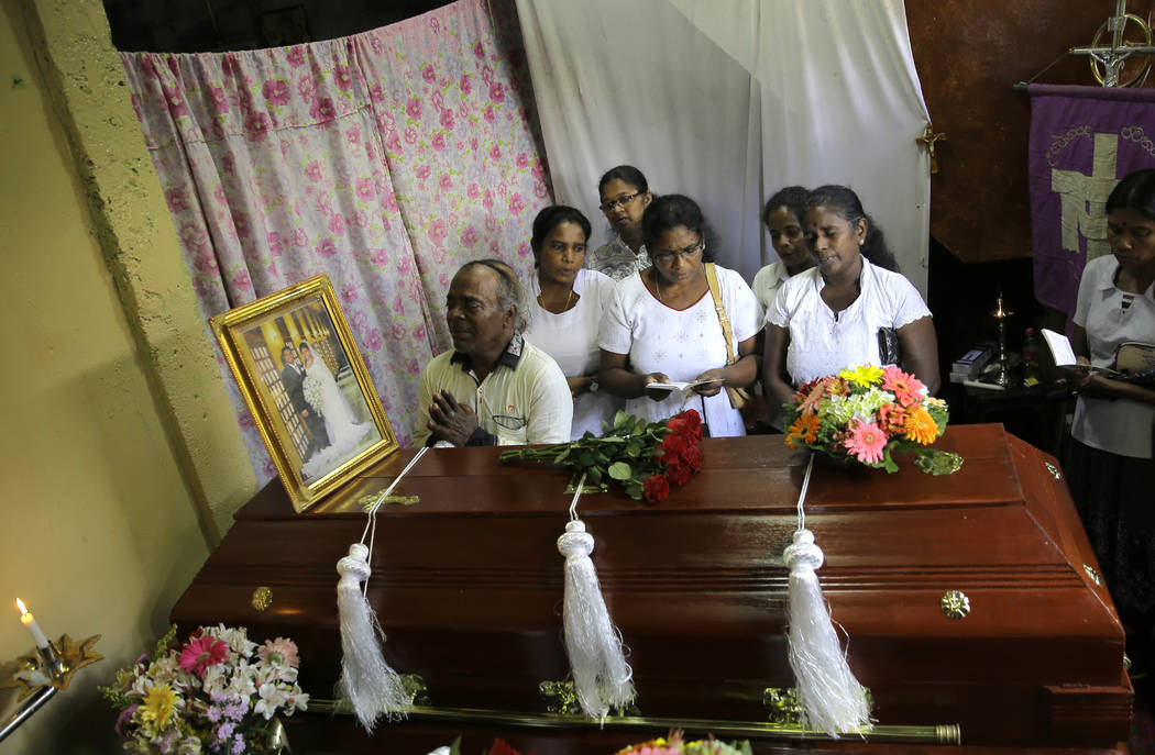 A Sri Lankan family mourns next to the coffin of their family member, a victim of Easter Sunday ...