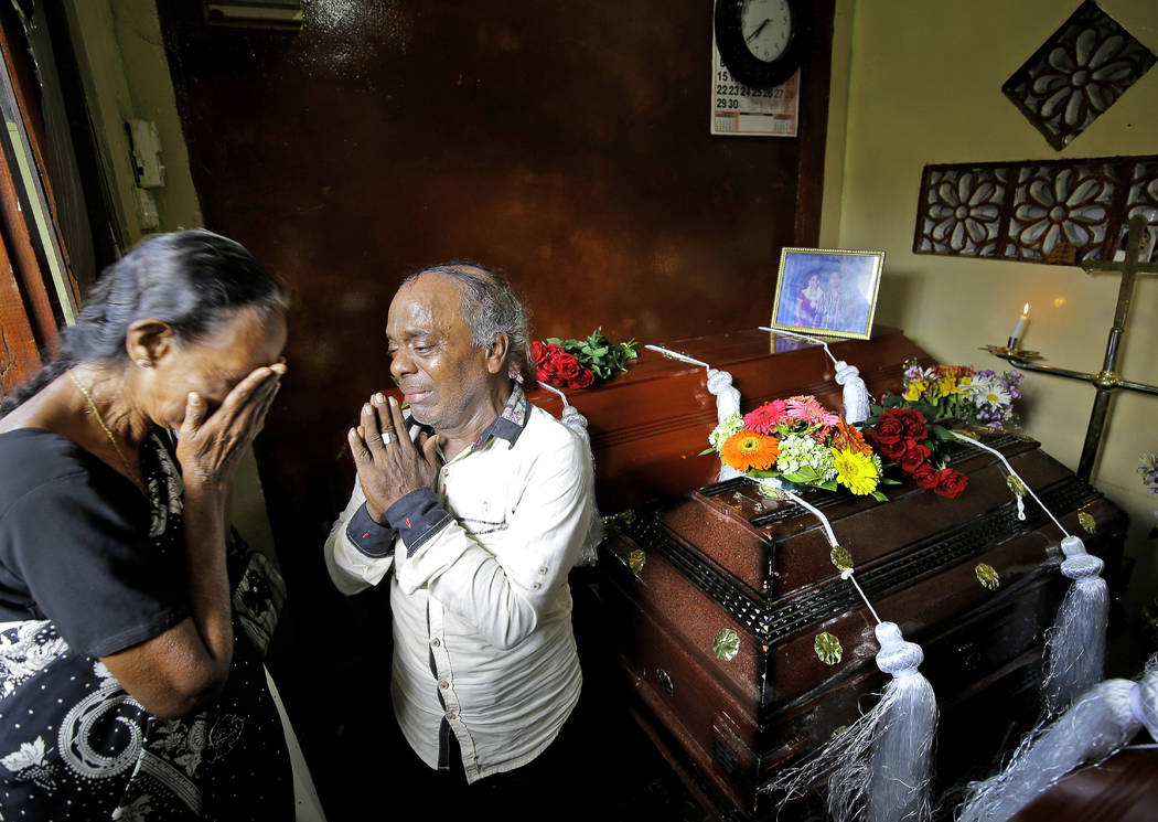 A Sri Lankan family mourns next to the coffins of their three family member, all victims of Eas ...