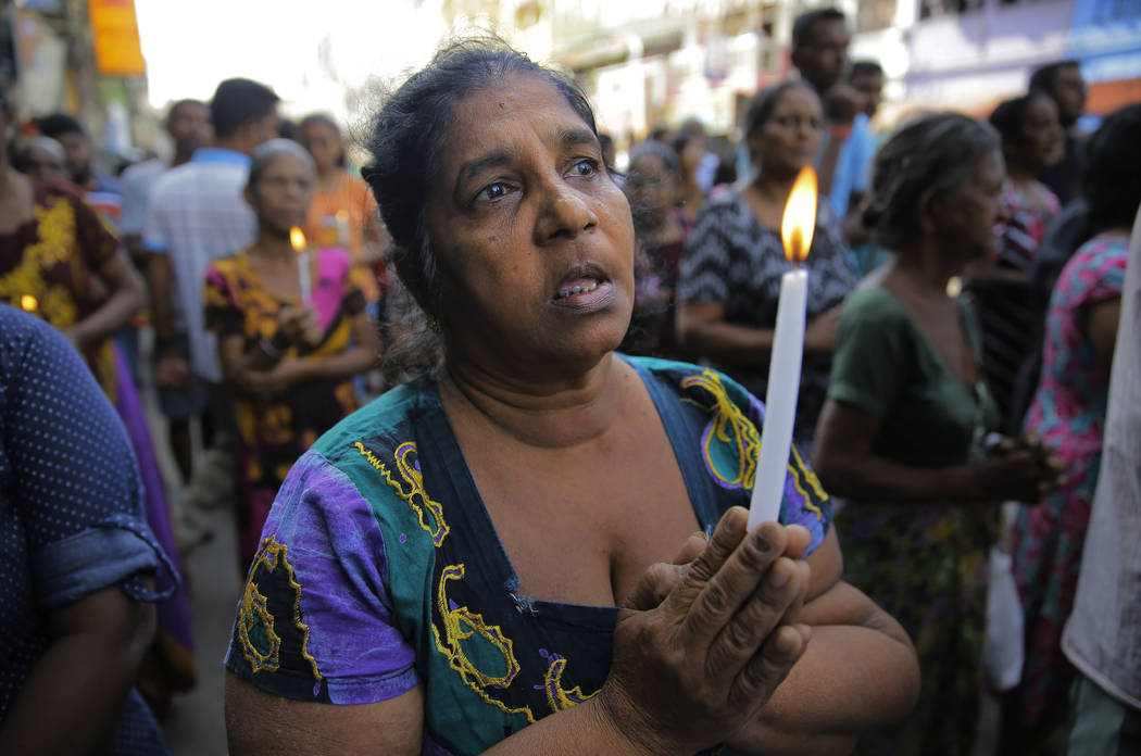 Sri Lankans pray during a three minute nationwide silence observe to pay homage to the victims ...