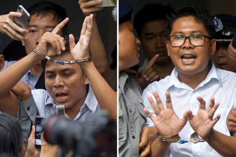 Reuters journalists Kyaw Soe Oo, left, and Wa Lone, are handcuffed as they are escorted by poli ...