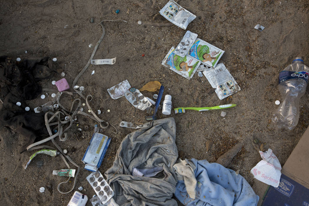 Personal hygiene products and medication lie on the side of the road after migrants were detain ...