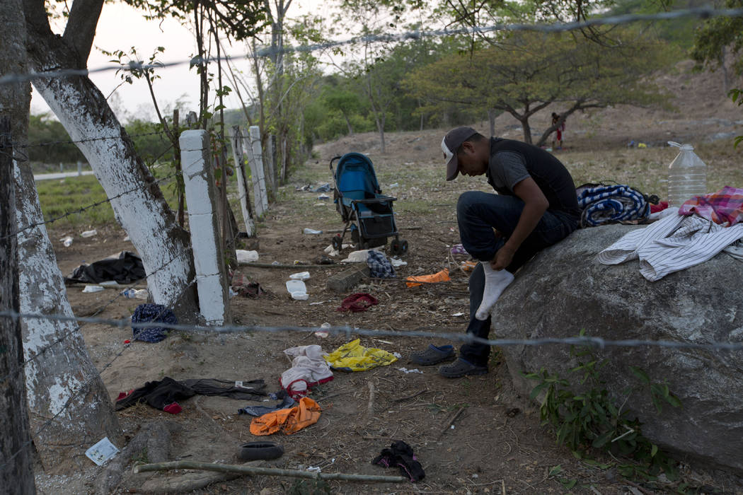 A migrant puts on the socks he'd left behind when his group evaded Mexican immigration agents b ...