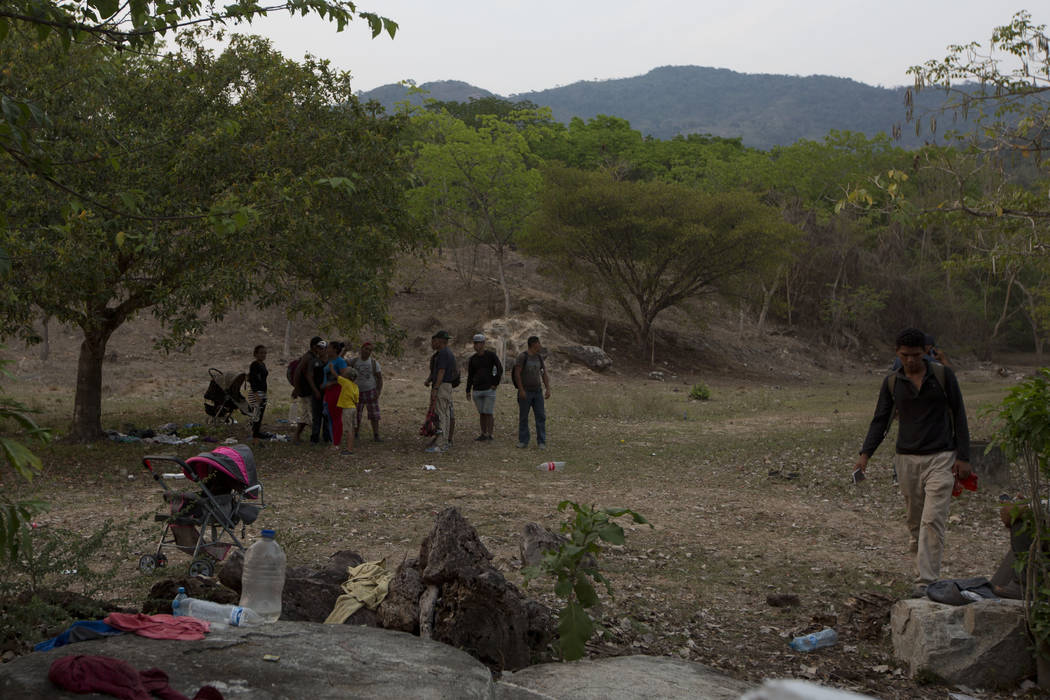 Central American migrants gather on the side of the road where others were detained earlier in ...