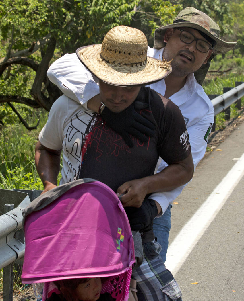 A Central American migrant pushing a child in a baby carriage is detained by a Mexican immigrat ...