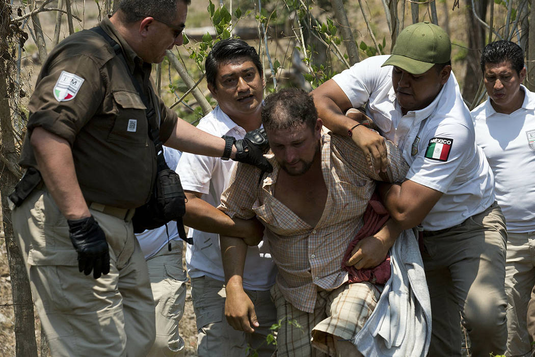 A Central American migrant is detained by Mexican immigration agents on the highway to Pijijiap ...
