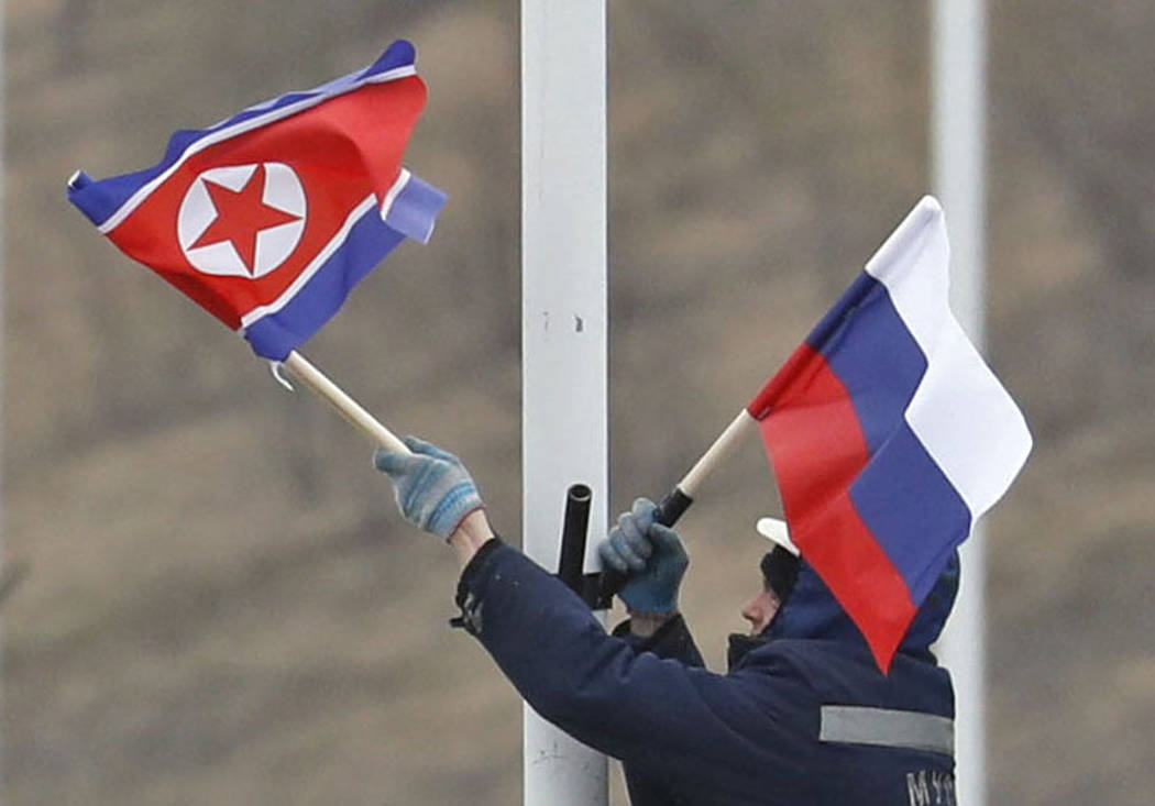 A worker adjusts the flag of Russia and North Korea along the road in Russky Island, off the so ...