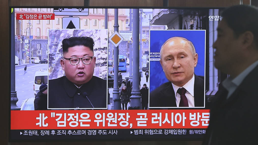 A man passes by a TV screen showing images of North Korean leader Kim Jong Un, left, and Russia ...