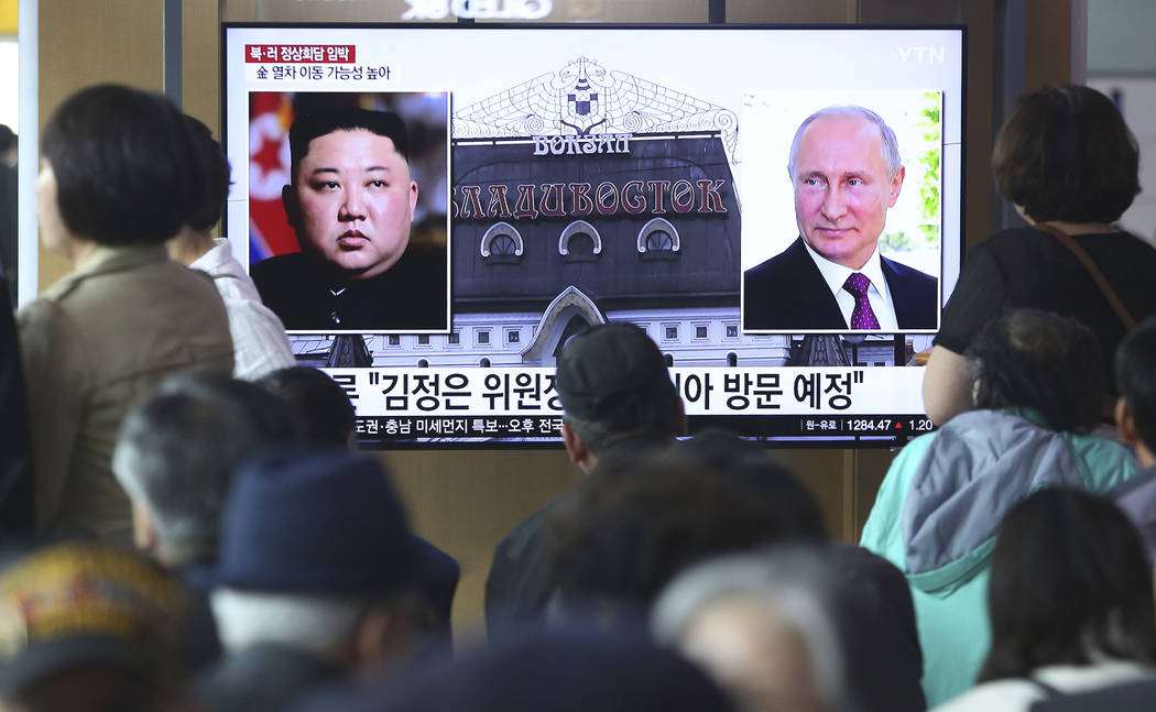 People watch a TV screen showing images of North Korean leader Kim Jong Un, left, and Russian P ...