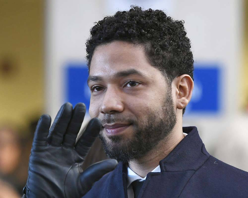 FILE - In this March 26, 2019, file photo, actor Jussie Smollett smiles and waves to supporters ...