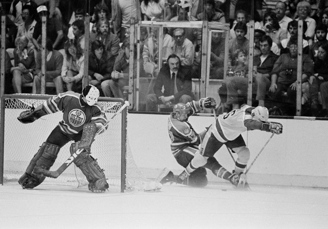 Edmonton Oilers' goal tender Grant Fuhr watches teammate Jari Kurri (17), center in dark unifor ...