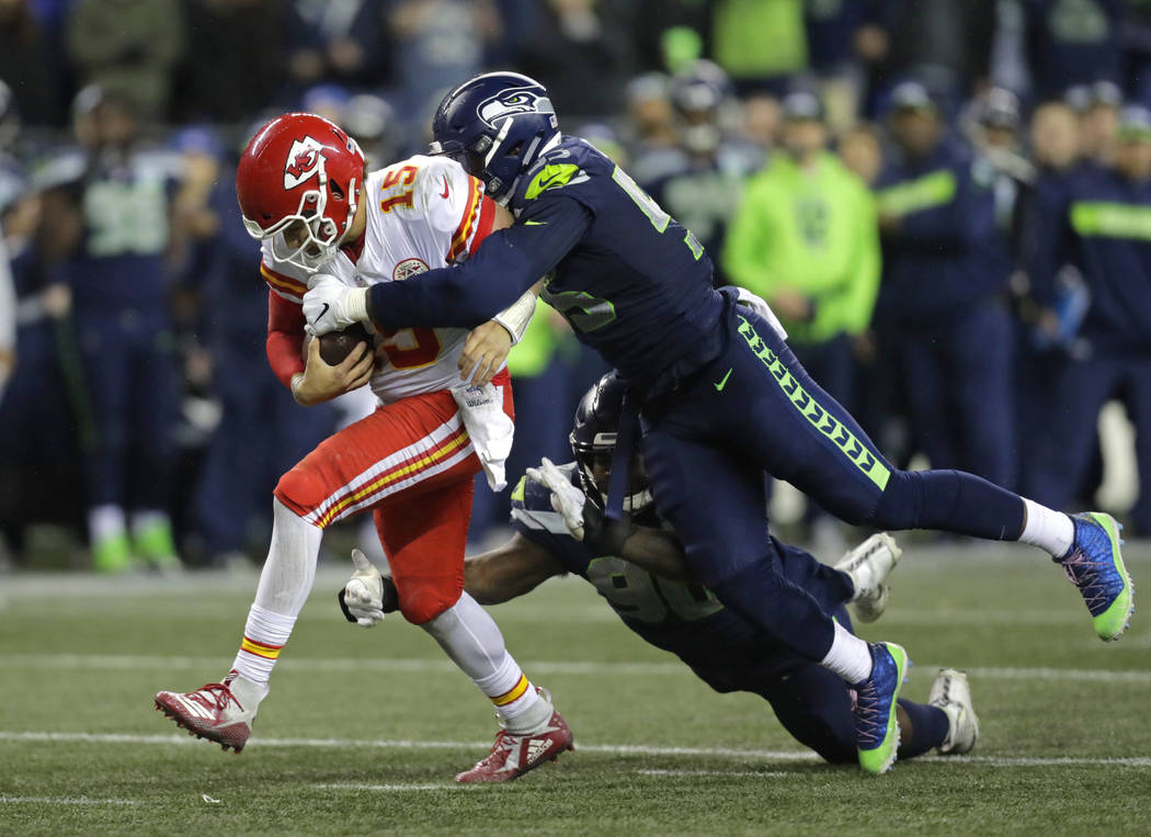 Kansas City Chiefs quarterback Patrick Mahomes (15) is tackled by Seattle Seahawks defensive en ...