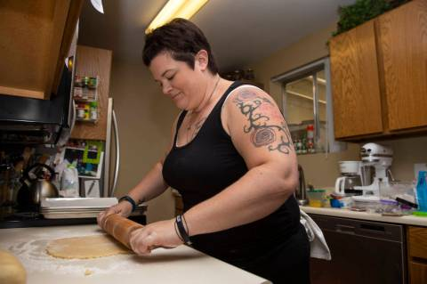 Owner of Cakes, Cookies and Creations Jessica Dejarnett rolls out dough to make sugar cookies i ...