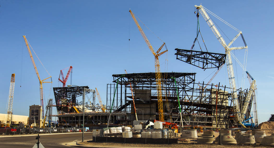 The newest truss is slowly lowered and attached into place atop of Raiders Stadium on Wednesday ...