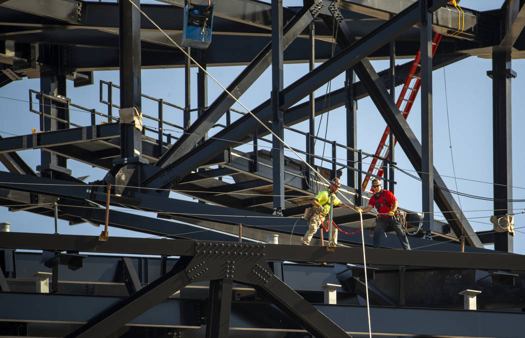 Crews work move the newest truss into place as its slowly lowered and attached into place atop ...