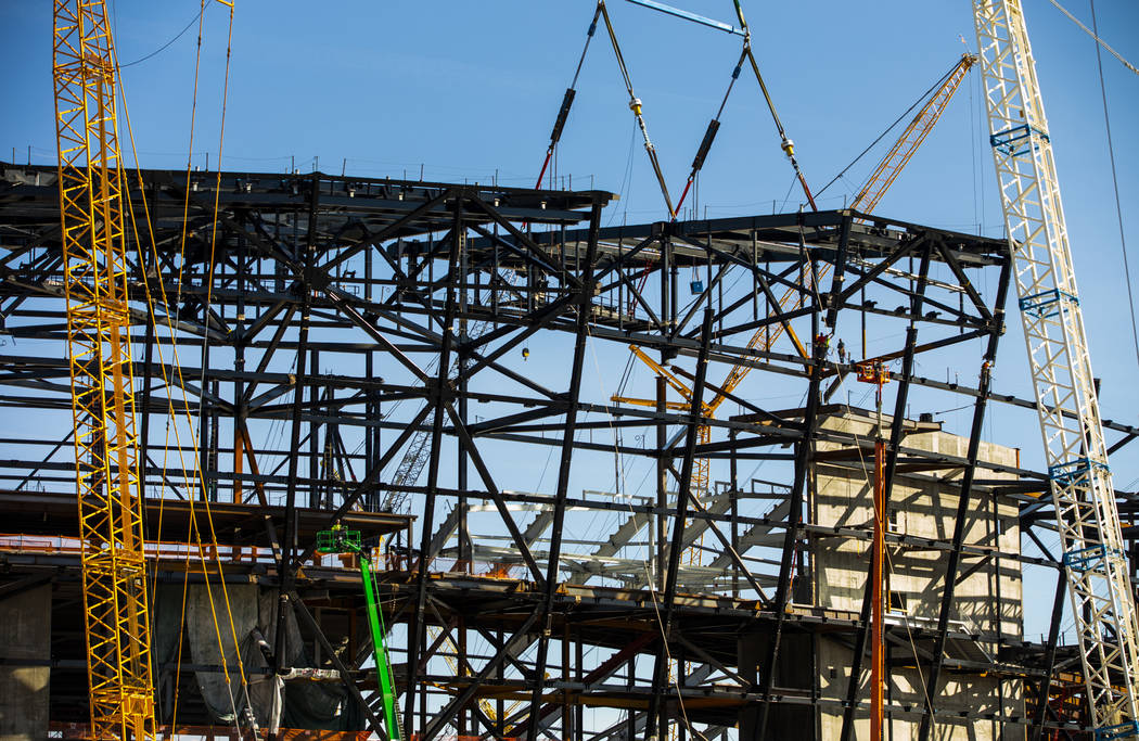 The newest truss is lowered into place and attached by awaiting steel worker ato top of Raiders ...
