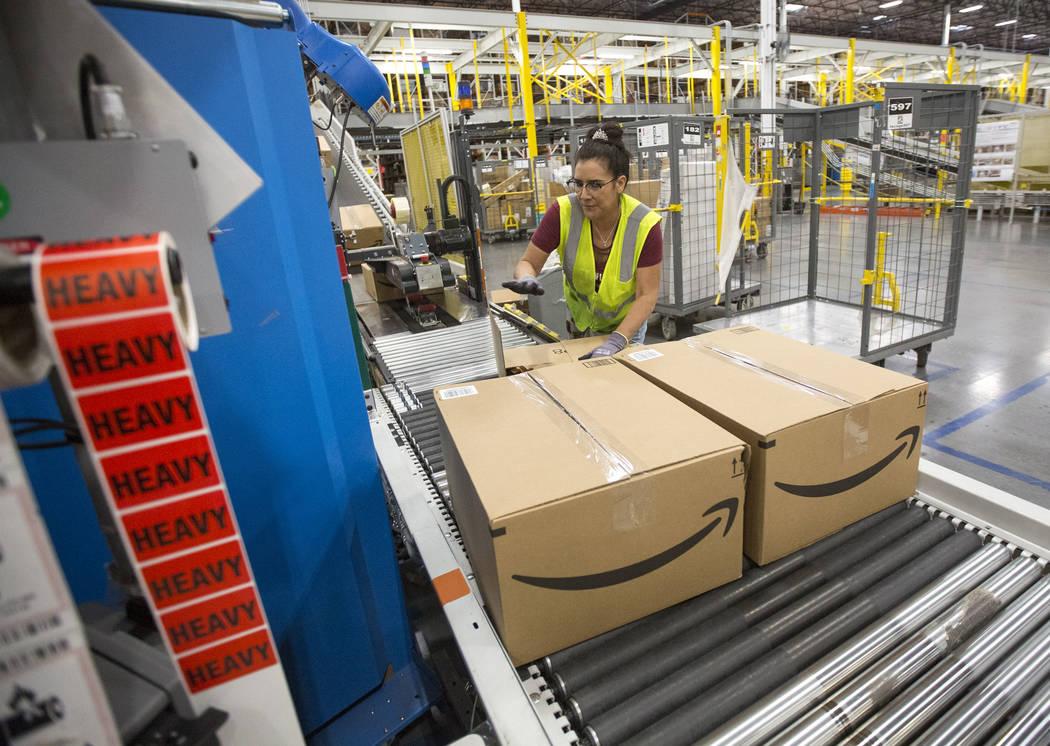 Sandee Moore packs customer orders moving on a conveyor belt at Amazon's North Las Vegas fulfil ...