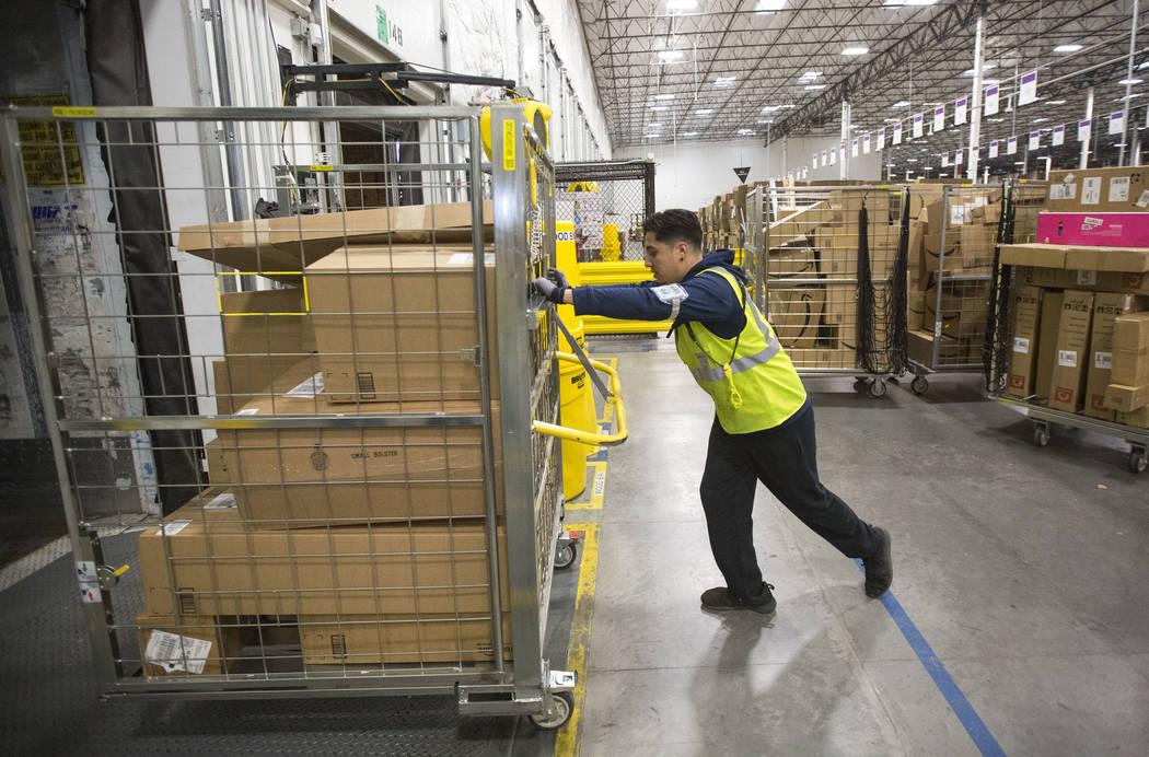 Eloy Zamudio loads customer orders onto a semitrailer at Amazon's North Las Vegas fulfillment c ...