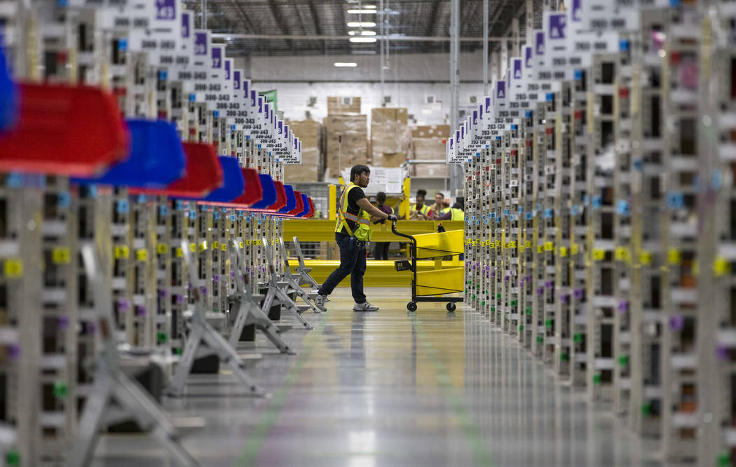 A worker navigates the aisles while preparing customer orders at Amazon's North Las Vegas fulfi ...